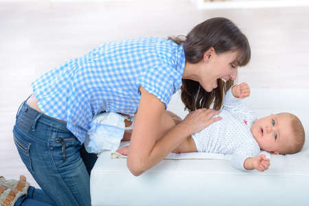 Photo pour woman playing with baby during nappy change - image libre de droit