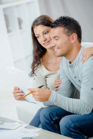 Photo pour young happy couple sitting on sofa calculating budget at home - image libre de droit