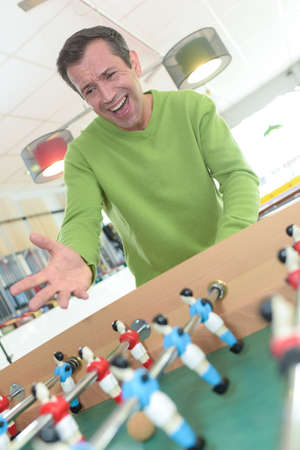 Photo pour one more goal cheerful young handsome man playing foosball - image libre de droit