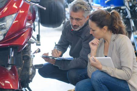 Photo pour mechanic giving diagnostic details to client - image libre de droit