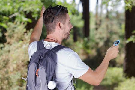 Photo pour rear view of male backpacker holding compass - image libre de droit