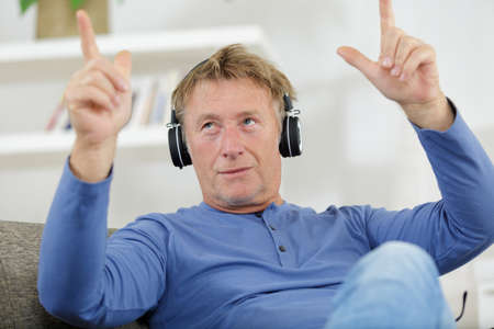 Photo pour middle aged casual man with headphone relaxing at home - image libre de droit