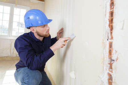 Photo pour male plasterer in uniform polishing the wall - image libre de droit