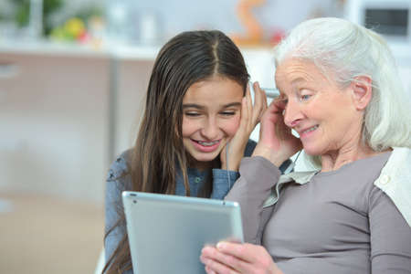 Photo pour Grandmother looking at tablet with granddaughter - image libre de droit