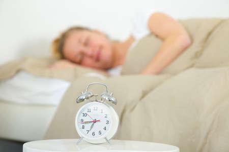 Photo pour attractive woman sleeping with the alarm clock - image libre de droit