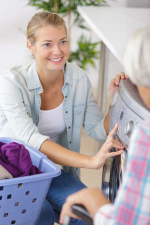 Photo pour woman assisting mother with washing machine at home - image libre de droit