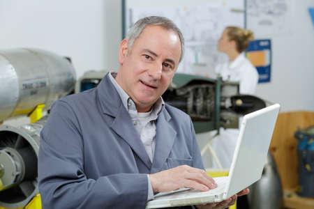 mature male technician using laptop