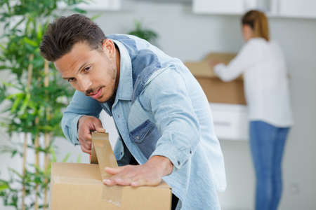 Photo pour man at home sealing box for dispatch - image libre de droit