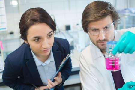 Photo pour scientists looking at pink liquid in glass flask - image libre de droit