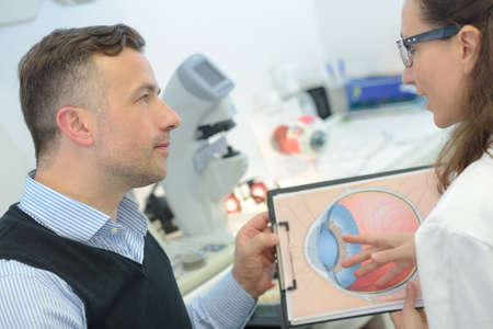 Photo pour doctor showing eye models to patient - image libre de droit
