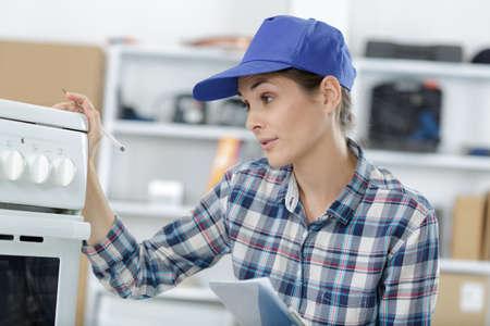 Photo pour woman inspecting electrical appliance - image libre de droit