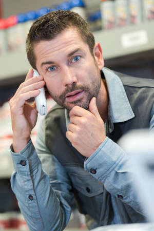 Foto de worker talking on telephone with a surprised facial expression - Imagen libre de derechos