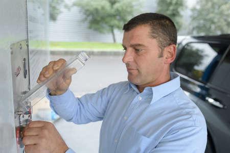 Photo pour person paying coins to self service automatic car - image libre de droit