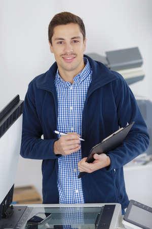 Photo pour portrait of man at photocopier holding clipboard - image libre de droit