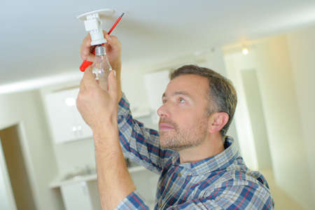 Photo for mature handyman changing bulb at clients home - Royalty Free Image