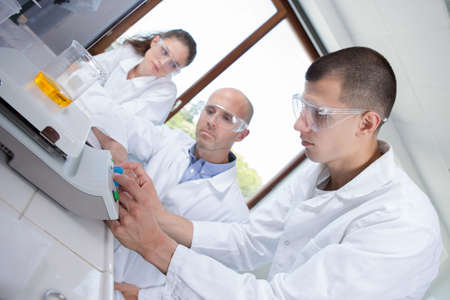 Photo pour young researchers working with chemical liquid in the laboratory - image libre de droit