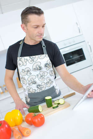 Photo pour handsome man cooking at home while checking tablet - image libre de droit