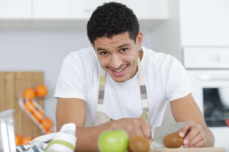 Photo pour a young man cutting tomatoes - image libre de droit