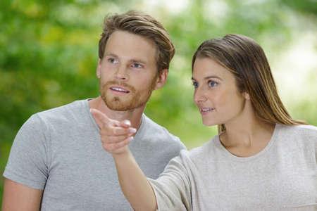 Photo pour portrait of a smiling happy couple pointing finger away - image libre de droit