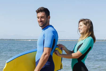 Photo pour woman is closing the wetsuit of a surfer - image libre de droit