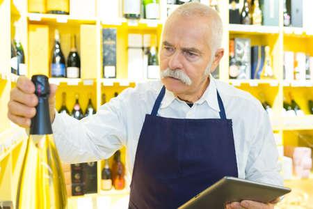Photo pour senior shop assistant in wine department holding digital computer - image libre de droit