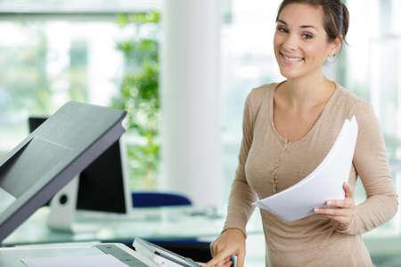 Photo pour happy woman photocopying in her office - image libre de droit