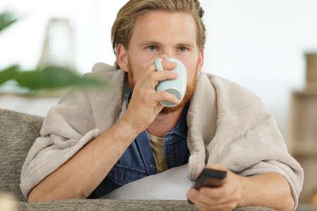 Photo pour man having his morning coffee on the sofa - image libre de droit