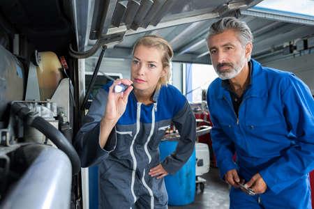 Photo pour male and female mechanic team examine an engine - image libre de droit