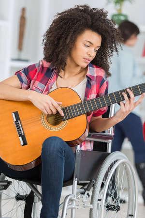 Photo pour a disabled girl playing guitar - image libre de droit