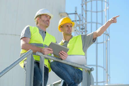 Photo pour workers on site holding tablet pointing into distance - image libre de droit