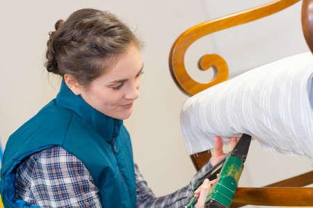 Photo pour woman using staple gun to uphlster a chair - image libre de droit