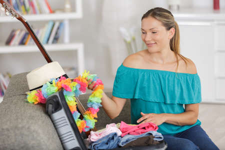 woman with suitcase on sofa nostalgically touching flower garland