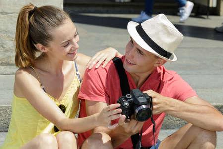 Photo pour A young couple checking out photos on the camera - image libre de droit