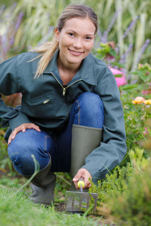 Photo pour positive female worker with gardening tools in the garden - image libre de droit