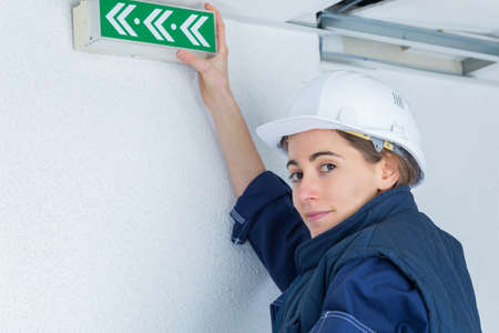 Photo pour worker placing exit signs hanging at a wall - image libre de droit