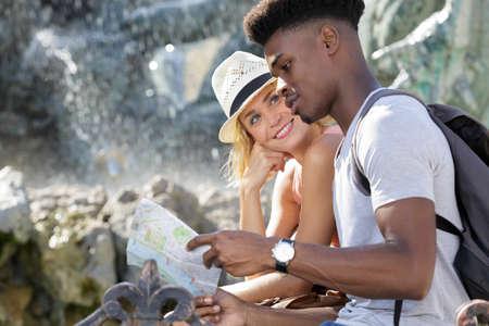 Photo pour multiracial group of friends looking at map - image libre de droit