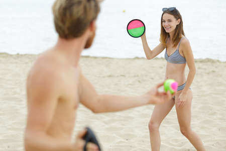 Photo pour couple playing sticky ball game at the beach - image libre de droit