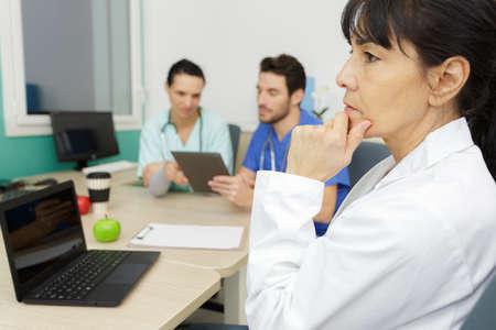 Photo pour senior woman doctor sitting with laptop in office interior - image libre de droit