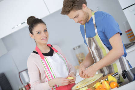 Photo pour beautiful couple in the kitchen a cake - image libre de droit