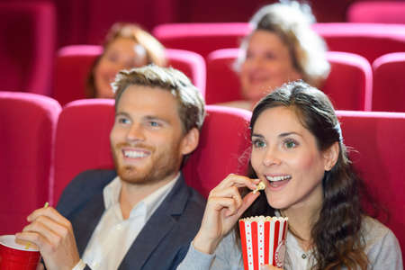 Photo pour happy couple eating popcorn while watching film at the cinema - image libre de droit