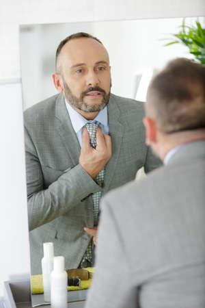 Photo pour man ties up a tie in front of a mirror - image libre de droit