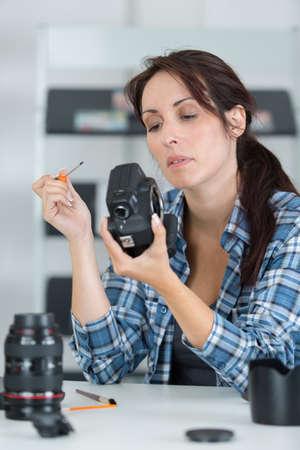Photo pour female photographer tuning her camera at studio - image libre de droit