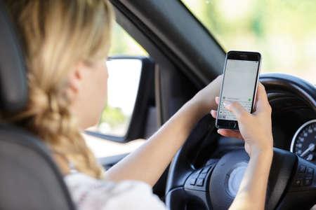 Photo pour young beautiful woman driving car while texting - image libre de droit