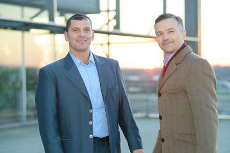 Photo pour male journalist interviewing businessman outdoors - image libre de droit
