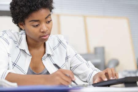 Photo pour a woman student holding calculator - image libre de droit