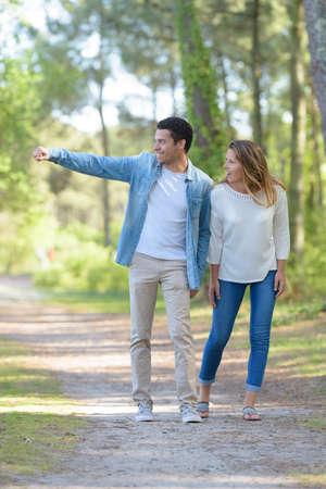 Photo pour young cheerful couple walking in the park - image libre de droit
