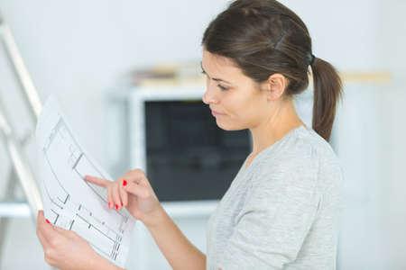 Photo pour portrait of woman studying the blueprint - image libre de droit