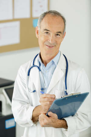 Photo pour senior doctor with clipboard looking at the camera - image libre de droit
