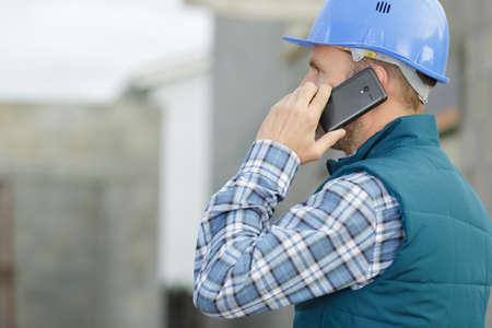 Photo pour portrait of male architect talking on mobile phone outdoors - image libre de droit