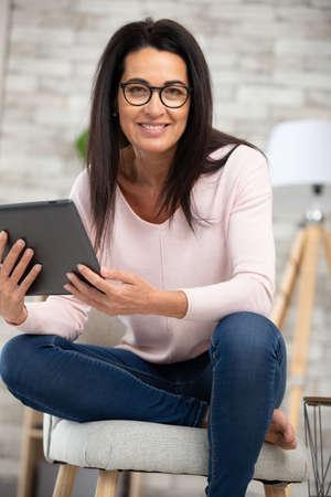 Photo pour mature woman browsing the internet with a digital tablet - image libre de droit